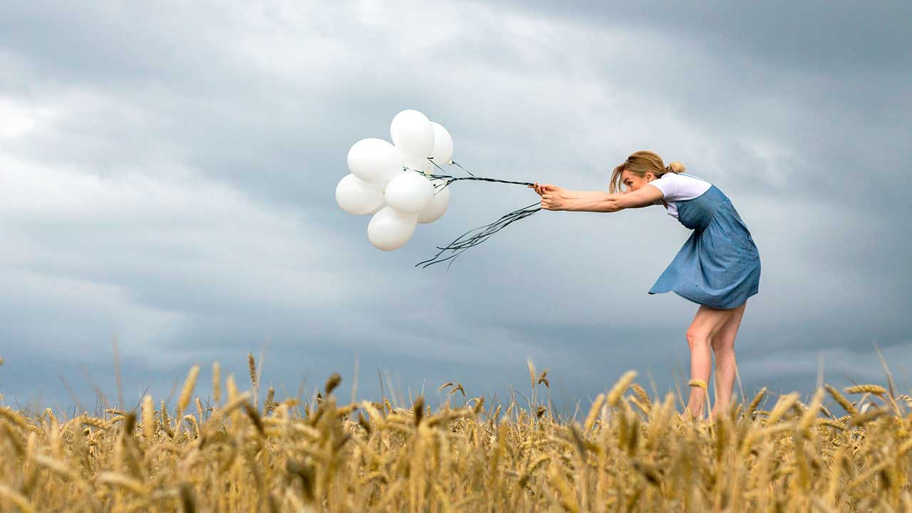 Frau hält Ballone gegen den Wind