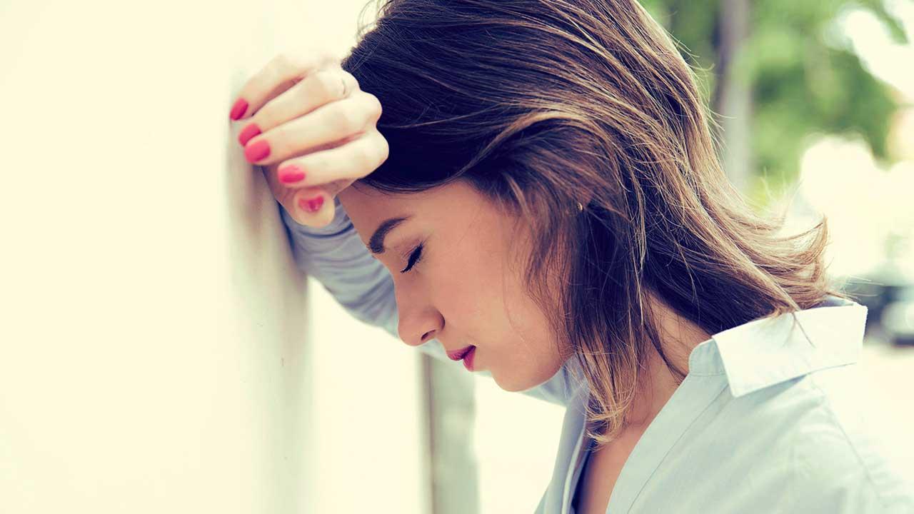 Ermüdete junge Frau an einer Wand