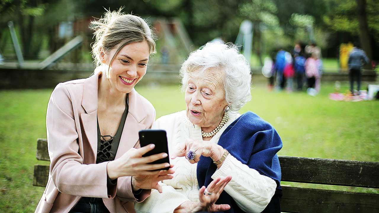 Junge Frau und Seniorin sitzen auf einer Parkbank und schauen gemeinsam etwas auf dem Smartphone an