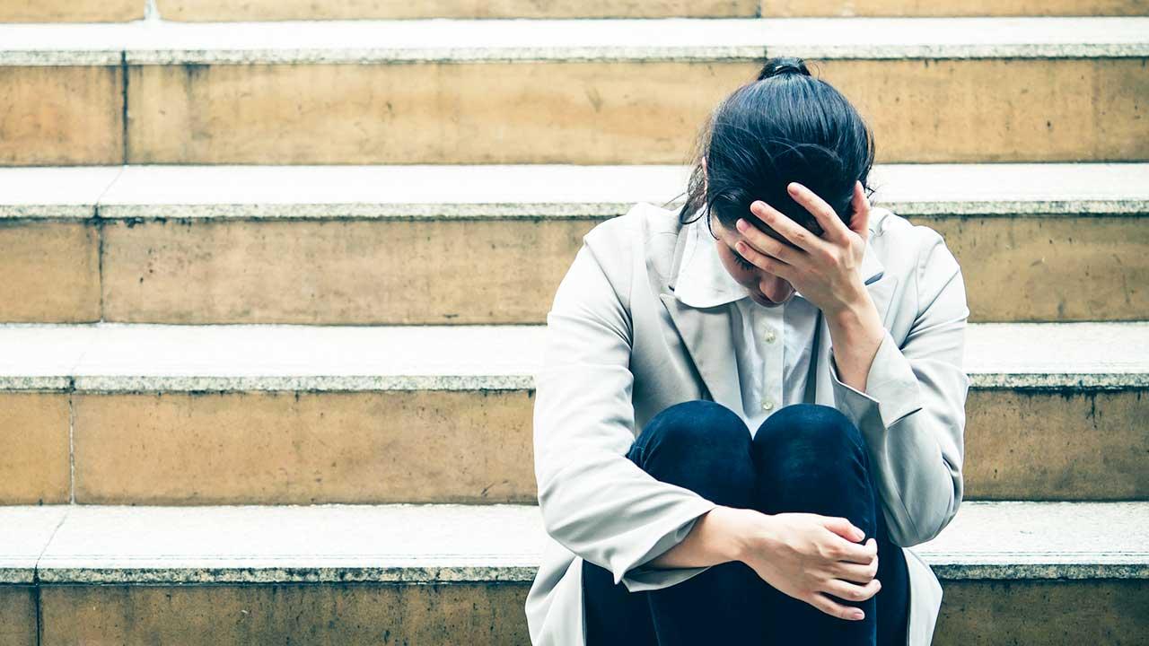 Geschäftsfrau sitzt auf einer Treppe, niedergeschlagen und getroffen