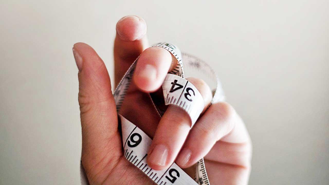 Hand hält ein verwickeltes Messband