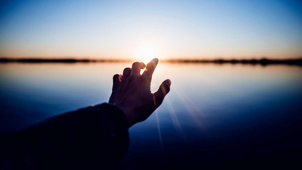 Hand streckt sich nach Sonnenstrahlen aus, welche sich am Horizont zeigen