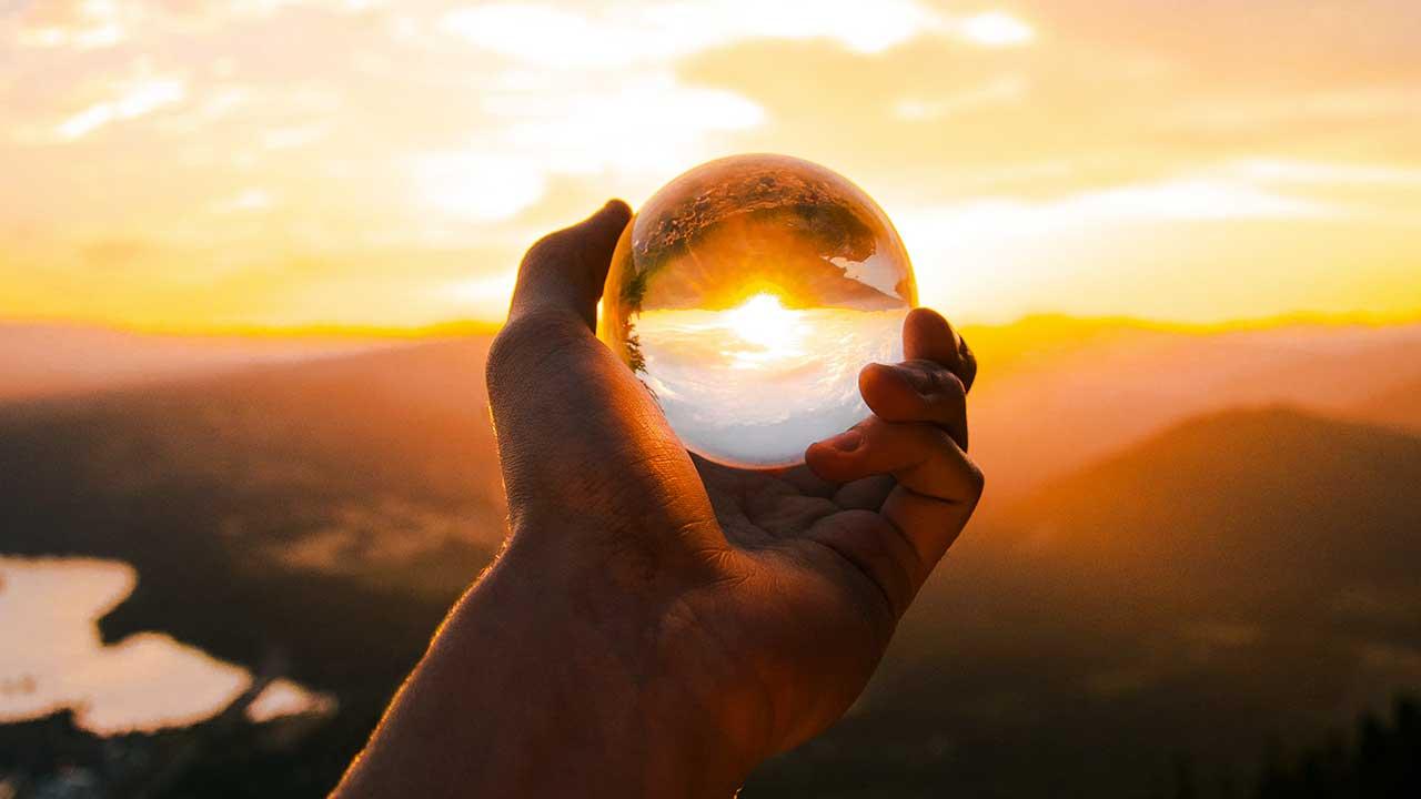 Hand hält Kristallkugel, welche vor einen Sonnenuntergang gehalten wird