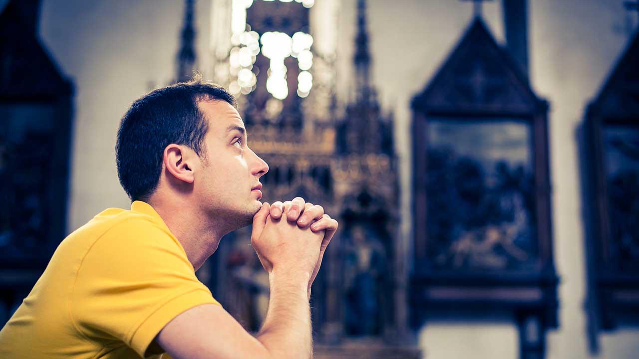 Junger Mann kniet in einer Kirchenbank und richtet seinen Blick nach oben