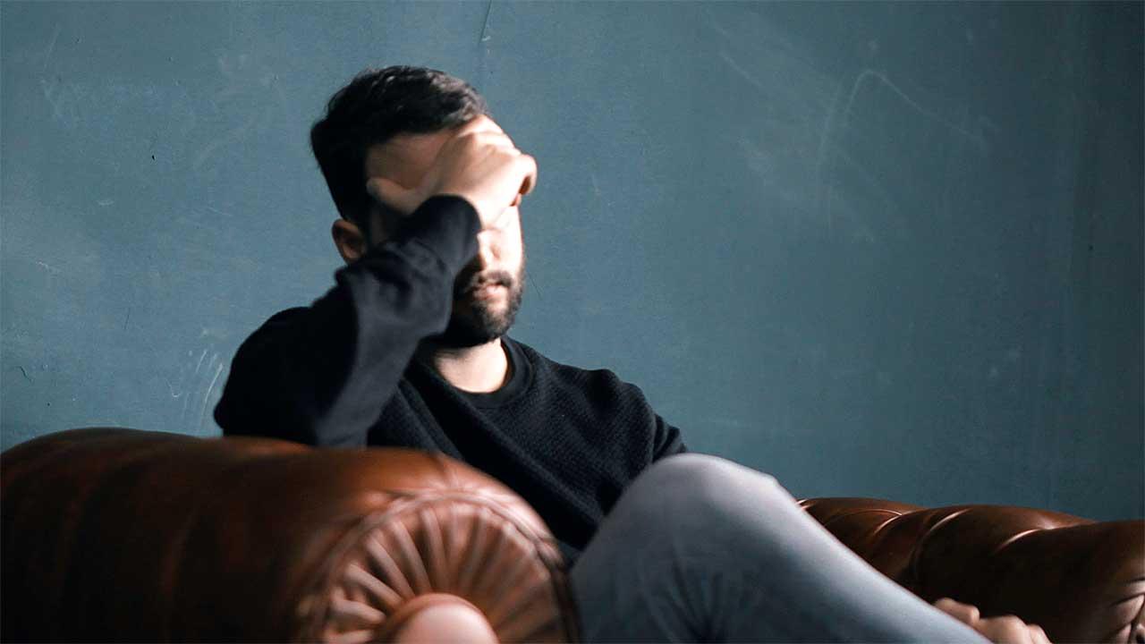 Mann sitzt resigniert auf Sofa