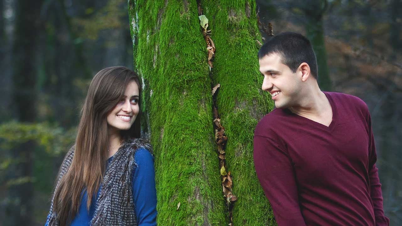 Eine Frau steht angelehnt auf der einen Seite eines Baums, der Mann auf der anderen