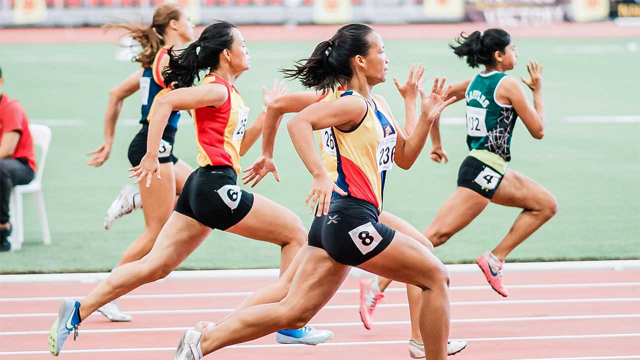 Sportlerinnen rennen auf einer Leichtathletikbahn