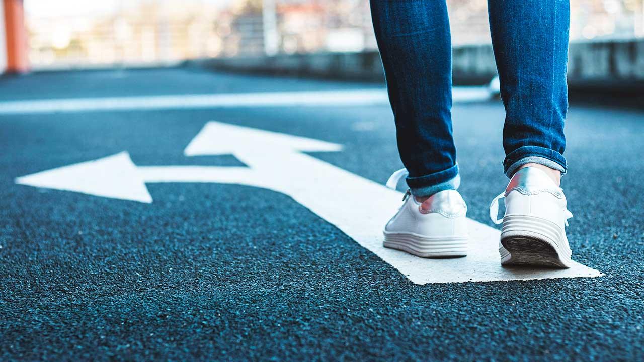 Person läuft auf einem Pfeil auf einer Strasse, von dem ein anderer abzweigt
