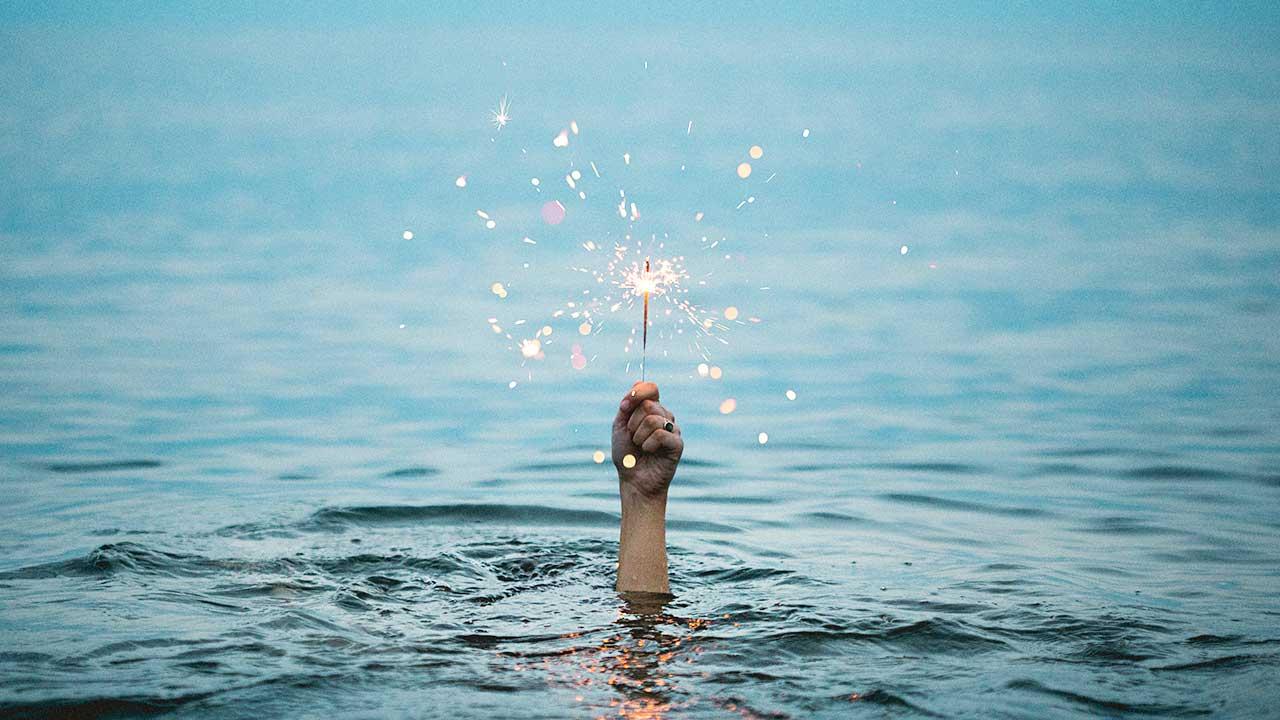 Hand steckt aus den Wasser und hält Wunderkerze in Händen